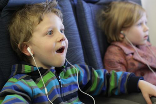 kids with earphones on airplane Blair Family