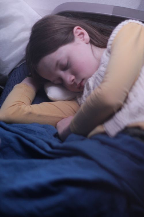 girl sleeping on airplane Maude Blair