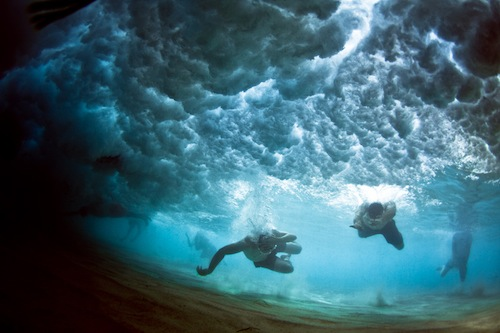 People Swimming under crashing waves
