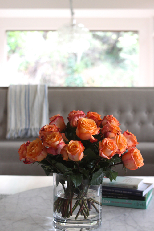 Fiery orange roses in a neutral living room.