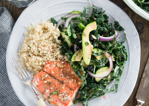 healthy dinner of salmon with kale salad and quinoa