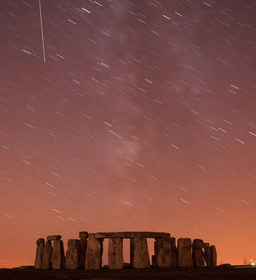 A meteor streaks past stars in the night sky over Stonehenge in Salisbury Plain