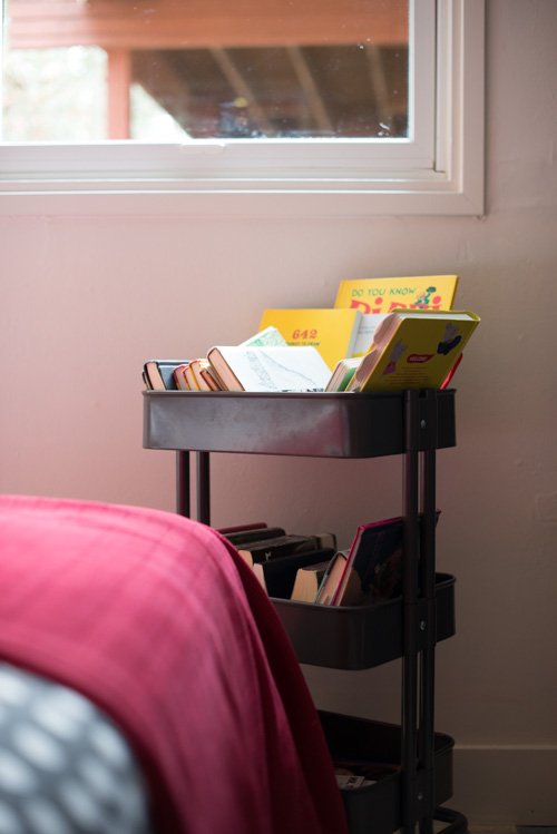 A shared bedroom for FOUR sisters. No room for a bookshelf, so a rolling library cart is used instead.
