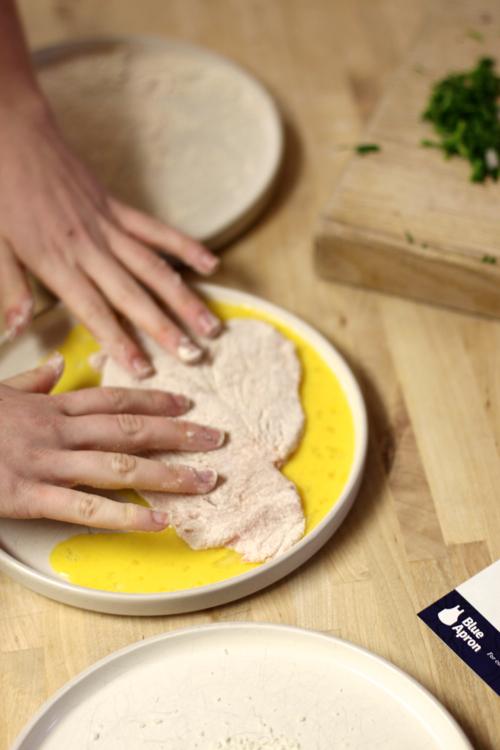 Making Schnitzel: flour then egg then breadcrumbs
